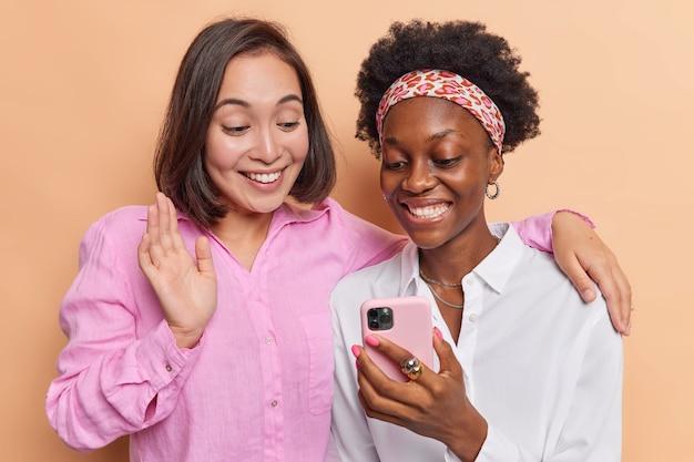 Les femmes s'amusent faire une vidéoconférence via un smartphone saluer un ami communiquer à distance embrasser et s'habiller avec désinvolture sur un mur marron utiliser les technologies modernes
