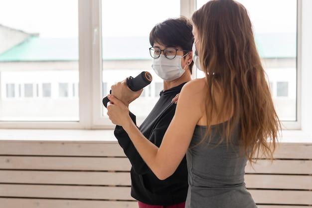 Des femmes s'entraînent ensemble après un traitement contre le coronavirus avec des masques faciaux