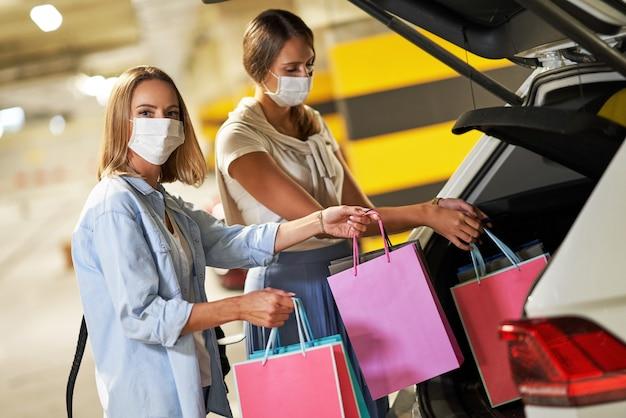 Femmes avec des sacs à provisions dans des masques dans un parking souterrain