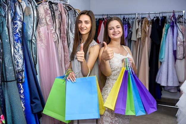Femmes avec des sacs à provisions en magasin de vêtements souriant