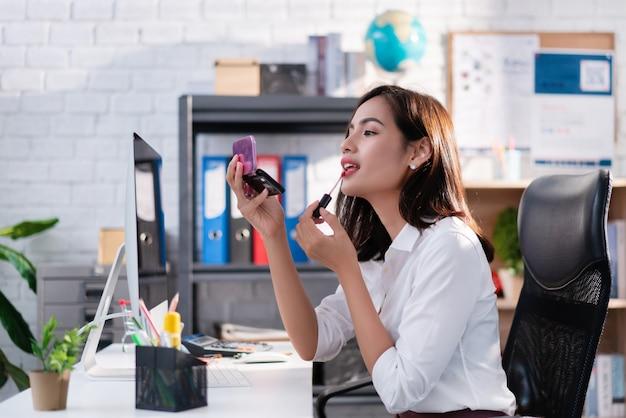 Les femmes se maquillent à son bureau pendant le travail