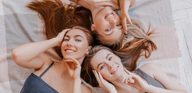 Les femmes se reposent et s'amusent. les copines rient à la maison allongées sur le sol sur des oreillers. les filles des arbres fabriquent des masques de beauté pour le visage et les cheveux faits maison. les femmes prennent soin d'une peau jeune.