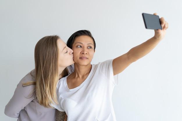 Femmes sérieuses s'embrassant et prenant une photo de selfie