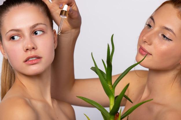 Les femmes avec un sérum pour la peau propre et hydratée et un spa de beauté de fleur d'aloe vera et concept de santé sur un mur blanc