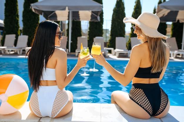 Femmes sexy avec cocktail assis au bord de la piscine sur le complexe, vue arrière. de belles filles se détendent à la piscine en journée ensoleillée, vacances d'été de copines séduisantes