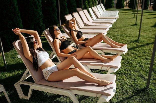 Femmes sexy en lunettes de soleil bronzer sur les transats à la piscine. de belles filles se détendent au bord de la piscine en journée ensoleillée, vacances d'été de copines séduisantes