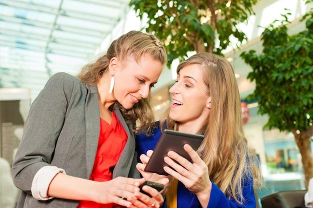 Femmes shopping avec des sacs au centre commercial