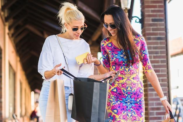 Femmes avec smatphone regardant des sacs et allant dans la rue commerçante