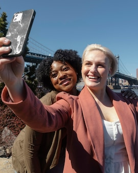 Femmes smiley à coup moyen prenant selfie