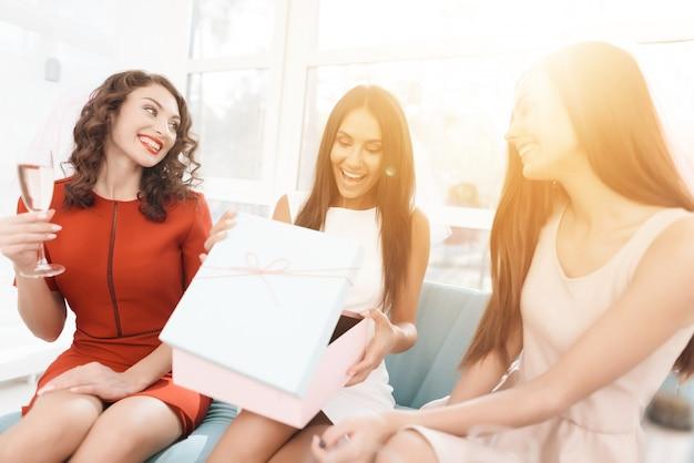 Les femmes sont assises sur le canapé avec une coupe de champagne.