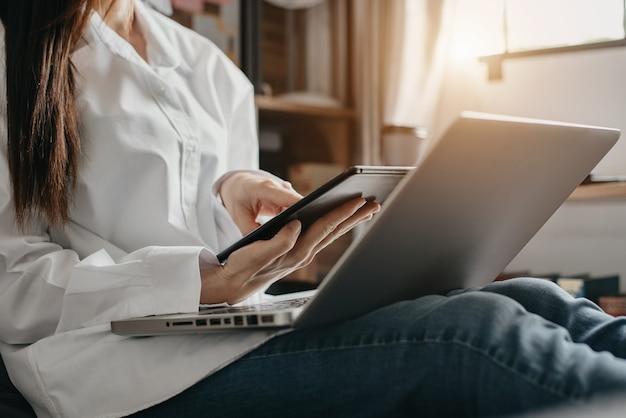 Les femmes sont assises à la recherche d'informations sur tablette et ordinateur portable le matin.