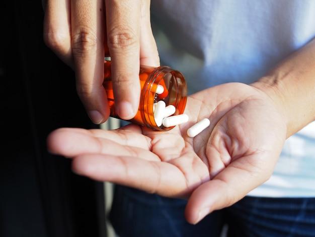 Les femmes souffrant d'inconfort et se sentant malades versent des médicaments dans la main pour manger et traiter la maladie. prenez des analgésiques.