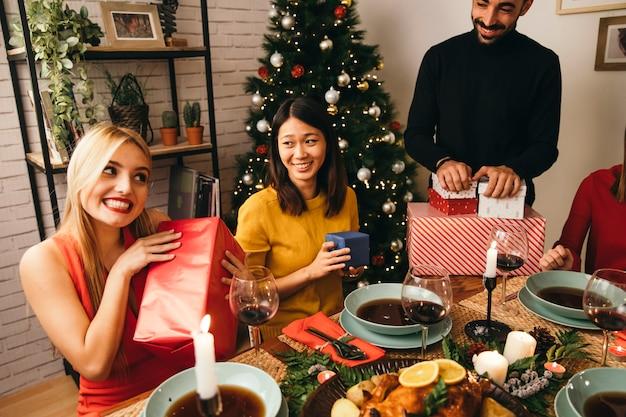 Femmes souriantes avec des cadeaux au dîner de noël