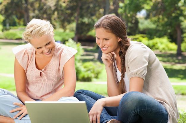 Femmes souriantes dans le parc avec un ordinateur portable