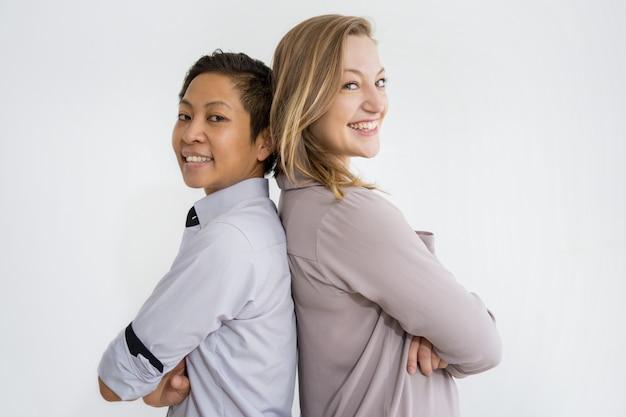 Femmes souriantes debout dos à dos