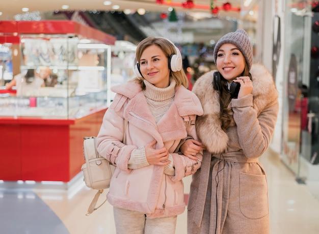 Femmes souriantes avec des écouteurs dans un centre commercial