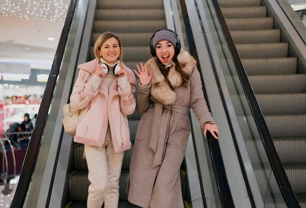 Femmes souriantes avec des écouteurs sur la tête sur l'escalator