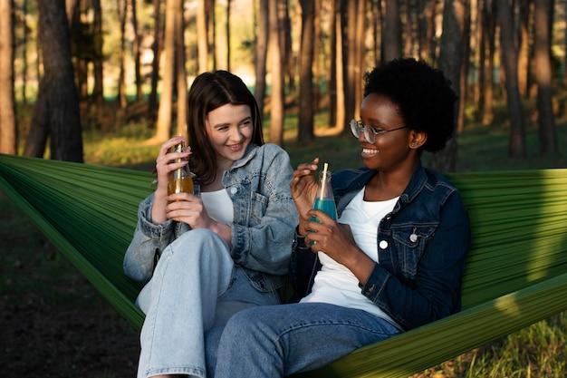 Femmes souriantes de plan moyen assis dans des hamacs