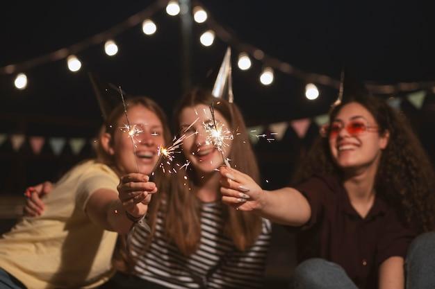 Femmes souriantes de plan moyen avec des feux d'artifice