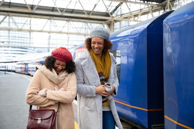 Femmes souriantes de plan moyen à la gare