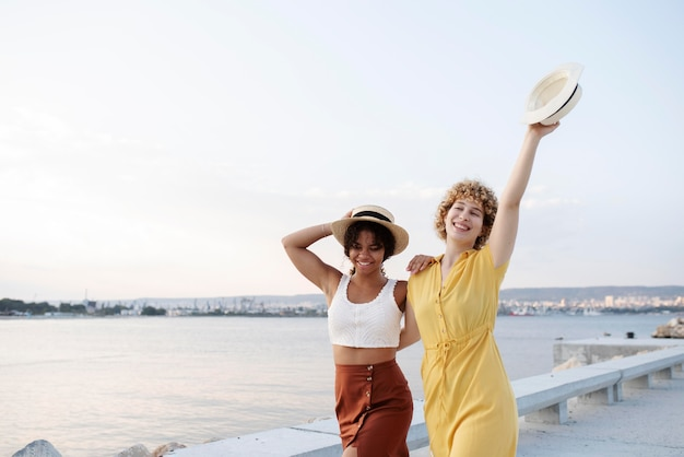 Femmes souriantes à plan moyen portant des chapeaux