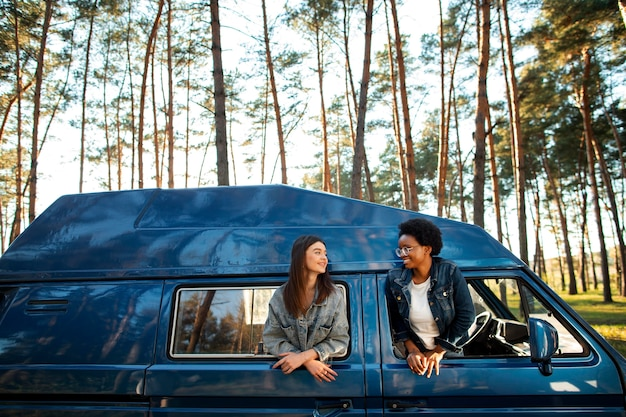 Femmes souriantes à plan moyen avec van