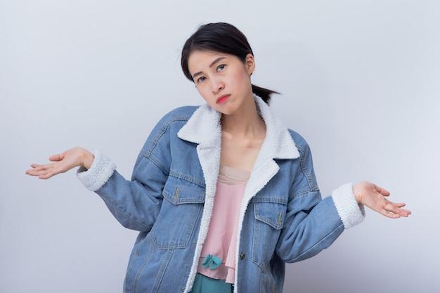 Femmes souriantes de race blanche pensant bad emotion jeune fille asiatique portant des vêtements décontractés bleus