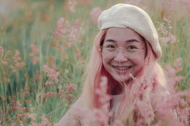 Les femmes sourient joyeusement lorsqu'elles sont assises dans le pré. , le visage de la jeune femme est heureux quand elle sourit.