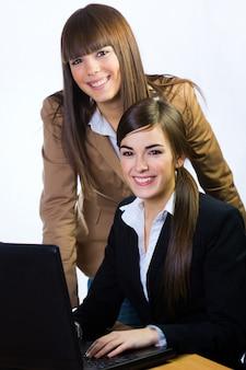Femmes sourire tout en travaillant sur ordinateur portable