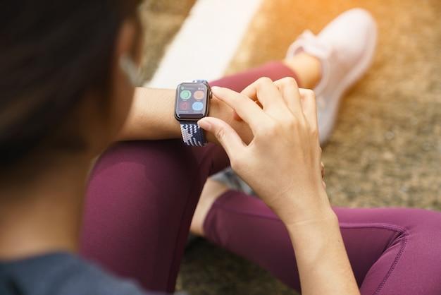 Les femmes de sport en gros plan vérifient sa montre intelligente
