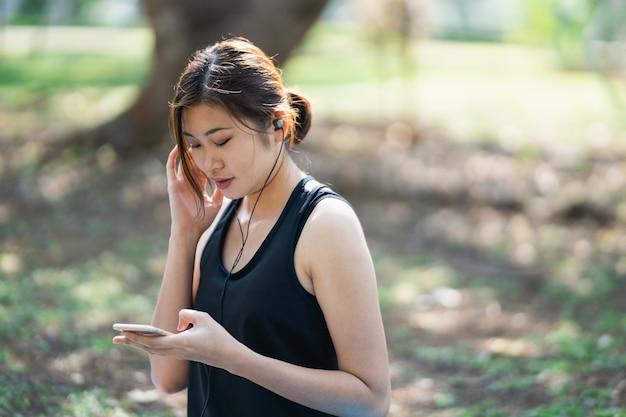 Femmes sportives écoutant de la musique avec des écouteurs dans le parc