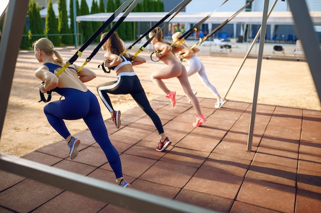 Femmes sportives, faire de l'exercice sur un terrain de sport à l'extérieur, vue arrière, entraînement de groupe à l'extérieur
