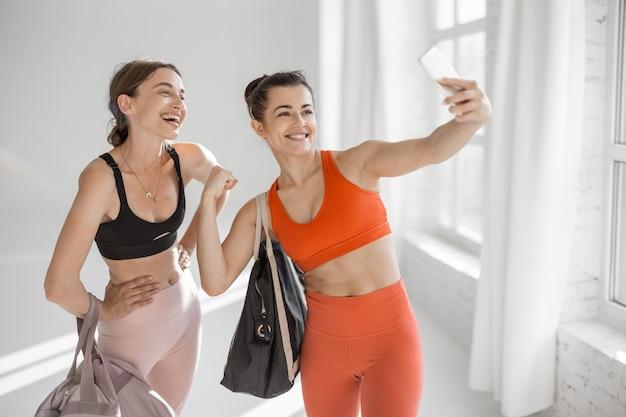 Femmes sportives faisant selfie au gymnase