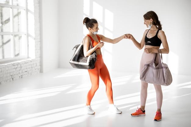 Des femmes sportives portant des masques faciaux se sont rencontrées dans la salle de sport