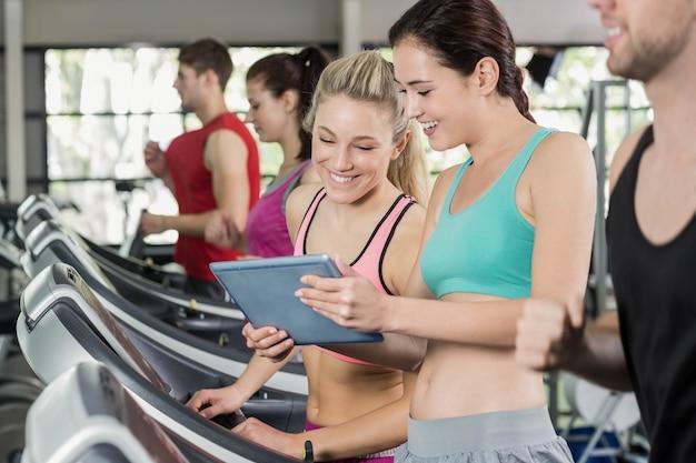 Femmes sportives regardant une tablette au gymnase