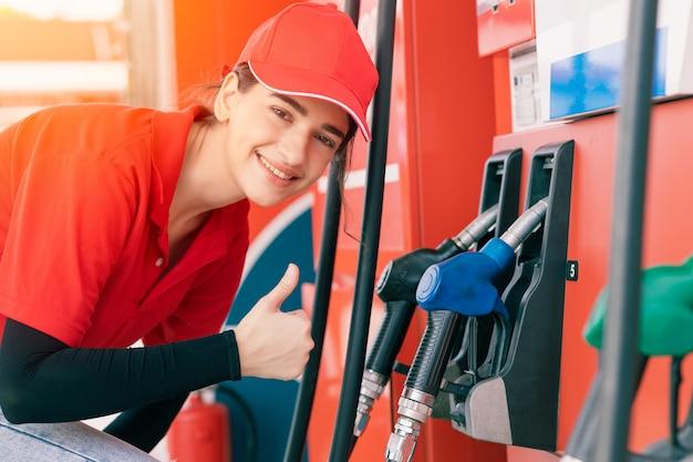 Les femmes de la station-service du personnel thumbs up à des distributeurs de buse de carburant service heureux de recharge de l'essence des voitures de travail