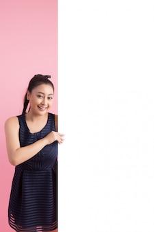 Femmes avec un tableau vide blanc, pointant loin