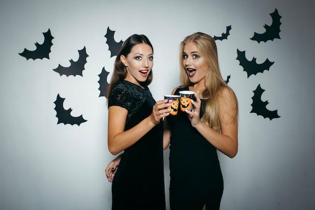 Femmes avec des tasses célébrant halloween