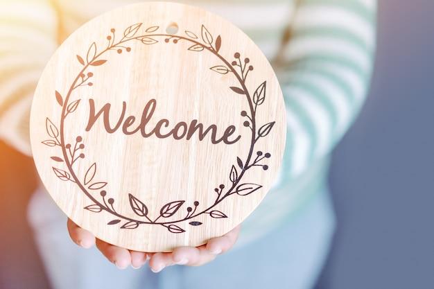 Femmes tenant le mot de bois de bienvenue bienvenue à la maison.