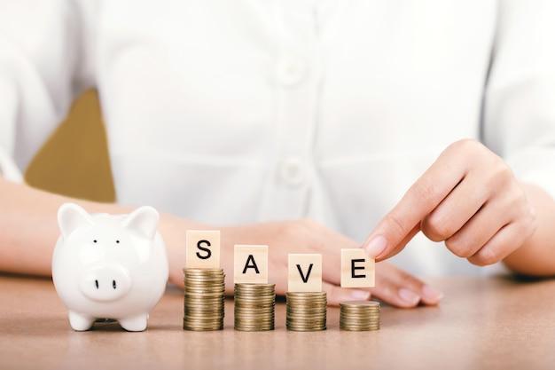 Femmes tenant le mot save sur les pièces empilées étape. concept d'économiser de l'argent pour l'avenir.