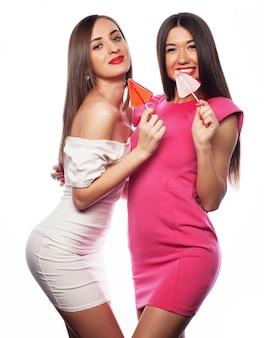 Femmes tenant une sucette rose et s'amuser ensemble