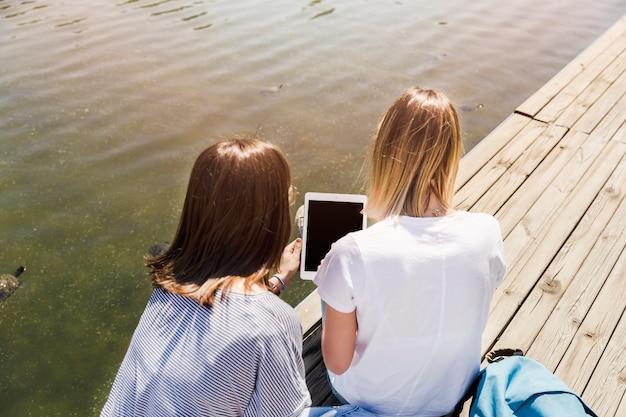 Femmes tenant une tablette près du lac
