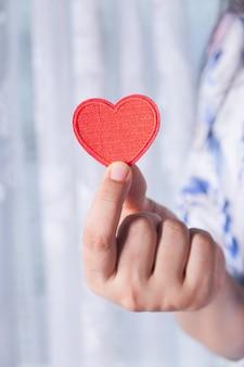 Femmes, tenue, coeur rouge, dans, mains, gros plan
