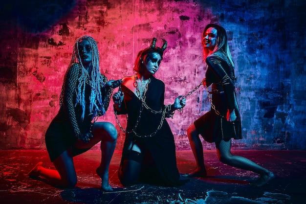 Femmes en tenue d'halloween posant avec sur fond bleu. une fille magnifique en vêtements célèbre le jour des morts. concept d'halloween, costume de sorcière, couleurs vives, filtre bleu.