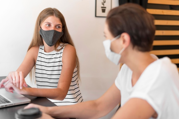 Femmes à la terrasse avec un ordinateur portable portant un masque