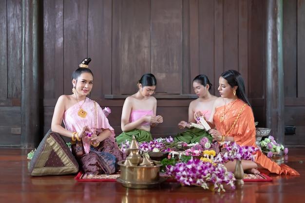 Des femmes thaïlandaises en costume traditionnel thaïlandais décorent des fleurs.