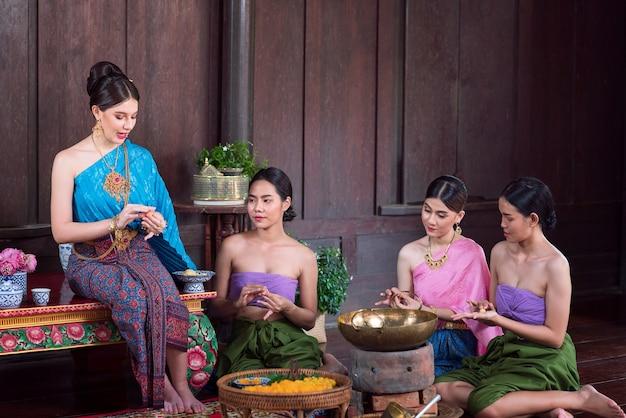 Femmes thaïlandaises en costumes anciens de la période ayutthaya dans une vieille maison avec des plats sucrés thaïlandais