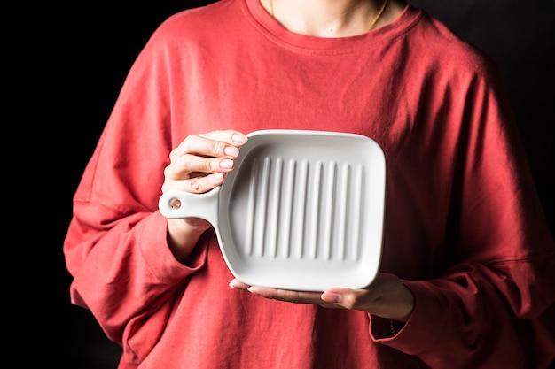 Les femmes tiennent des assiettes blanches dans leurs mains.