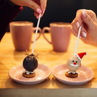 Les femmes tiennent des bâtons avec des bonbons en forme de noël sur des assiettes roses