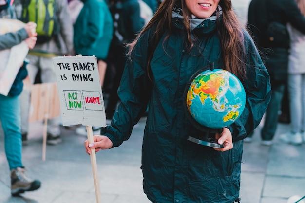 Les femmes tiennent un globe terrestre et une bannière avec la phrase